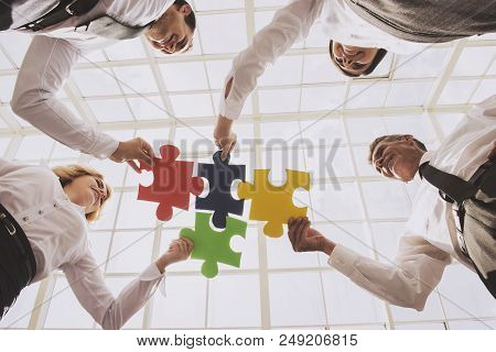 Group Of Business People Assembling Jigsaw Puzzle. Team Building Activities. Bottom View. Four Smart