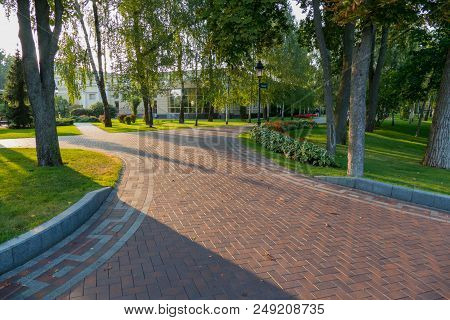 A Wide Park Walkway With Decorative Green Trees Near The Modern Building