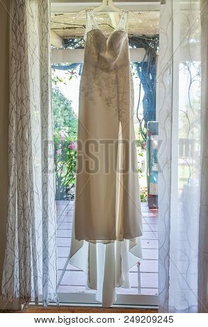 Empire Spaghetti Strap White Wedding Dress With Lace Bodice Glowing As Morning Sunlight Shines Throu