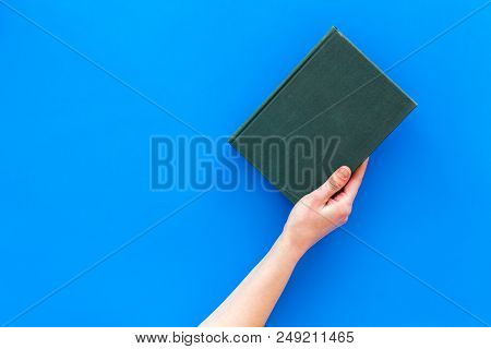 Reading For Leasure. Hands Take Hardback Book With Empty Cover On Blue Background Top View.