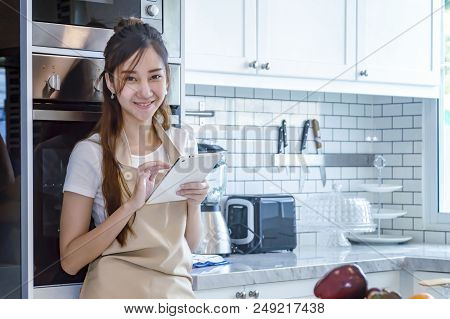 Beautiful Young Woman Is Using A Digital Tablet And Smiling While Cooking In Kitchen At Home
