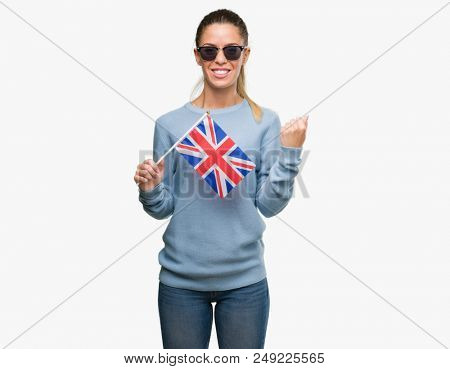 Beautiful young woman holding UK flag screaming proud and celebrating victory and success very excited, cheering emotion