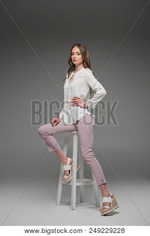 Elegant Female Model Sitting On Chair And Looking At Camera On Grey Background