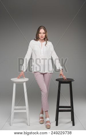 Elegant Woman Posing Between Two Chairs On Grey Background