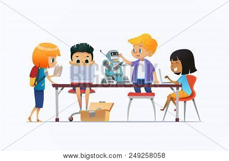 Boys And Girls Standing And Sitting Around Desk With Laptops And Robot And Working On School Project