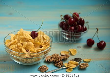 Tasty Cornflakes With Walnut And Cherry In Glass Bowl On Blue Background. Corn Flakes, Copy Space