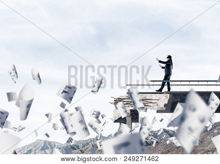 Businessman Walking Blindfolded Among Flying Papers On Concrete Bridge With Huge Gap As Symbol Of Hi