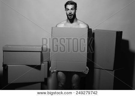 Sexuality And Moving Concept. Loader With Shocked Face Covers Nudity. Man With Beard Stands On Pink