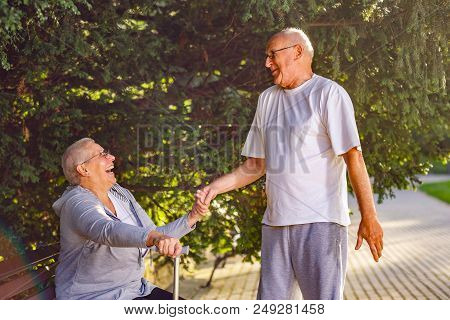 Seniors In Park- Smiling Old Man Caring Wife In The Park