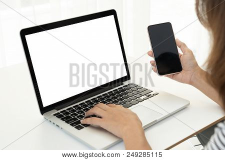 Back View. Young Business Woman Sitting In Office At Table And Using Smartphone. On Desk Is Laptop A