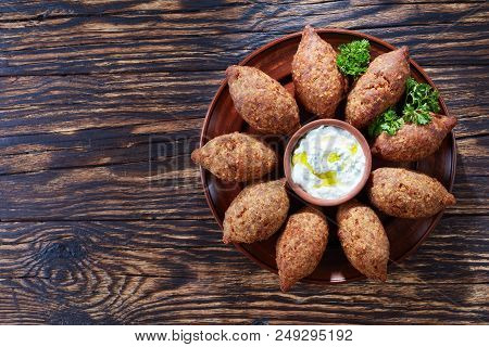 Delicious Fried Kibbeh With Yogurt Sauce In A Bowl Served On A Clay Plate On An Old Dark Wooden Tabl