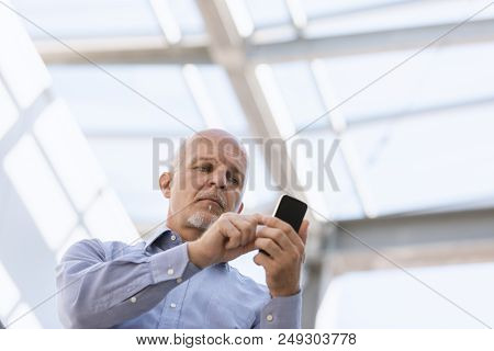 Low Angle View Of Man Texting On His Mobile