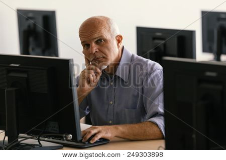 Mature Man Looking At Camera While Working
