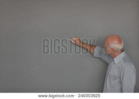 Male Teacher Writing On Chalkboard