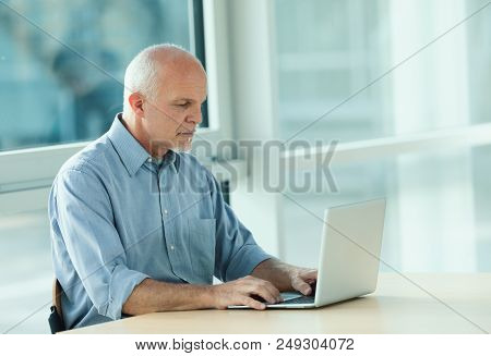 Man Seated At Desk Working On Laptop