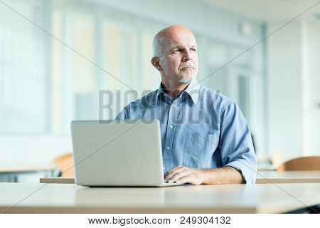 Man Seated In Front Of Laptop Computer