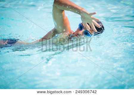 Man swimmer swimming crawl in a blue water  pool. Portrait of an athletic young male triathlete swimming crawl wearing swimming goggles. Triathlete training for triathlon.