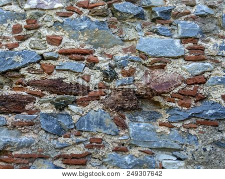 Old Wall To Face View Made With Pieces Of Bricks And Stones
