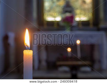 The Flame Of A Candle Illuminates A Church