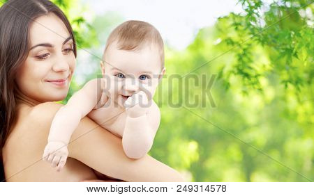 family and motherhood concept - happy smiling young mother with little baby over green natural background