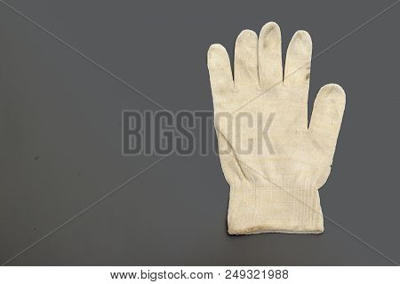 White Knitted Working Glove With Stretchable Cuff On The Dirty Gray Background. With Clipping Path