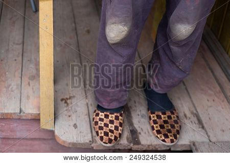 Man In Warm Shabby Slippers On The Background Of Old Wooden Floor.