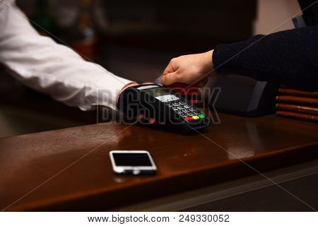 Payment With Credit Card. Male Hand Puts Bankcard Into Reader On Defocused Background. Credit Card T