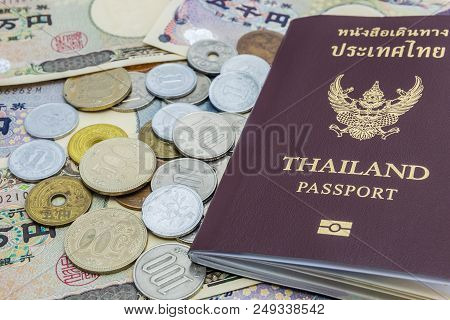 Closeup Of Japanese Yen Banknotes And Japanese Yen Coin With Thailand Passport. Financial Money And