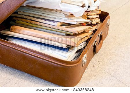 Old fashioned suitcase made of leather is full of folders, papers and documents, overloaded. poster