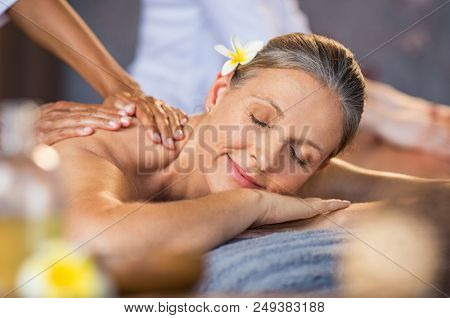 Woman lying on a spa bed and getting a relaxing massage. Serene mature woman having oil massage on her back. Portrait of senior woman with closed eyes having spa treatment.