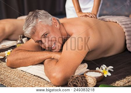 Senior man relaxed in spa while having a back massage. Happy mature man feeling relaxed and looking at camera. Male beauty therapy concept.
