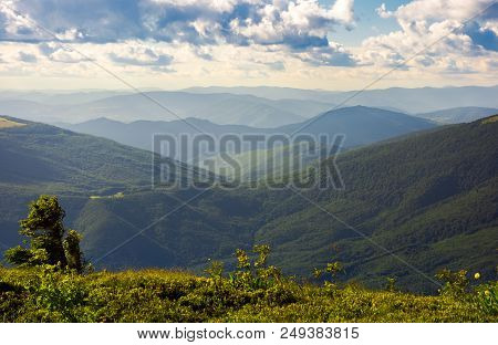 Rolling Hills On A Cloudy Summer Afternoon. Fluffy Clouds Over Distant Mountain Ridge. Mountainous L