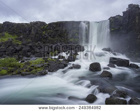 Oxararfoss Waterfall In Thingvellir Iceland Nature Reserve With Volcanic Rocks And Moss, Falling Fro