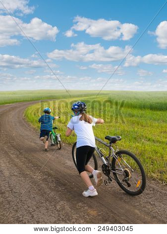 Sporty Kids Walking Uphill With Bikes On Rural Landscape Together