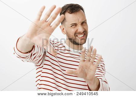Turn Off Light It Is To Shiny. Displeased Uncomfortable Handsome Adult Man In Striped Outfit Pulling