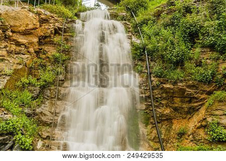 Beautiful Natural Waterfall Cascading Down A Mountain Hillside Covered In Lush Green Foliage,