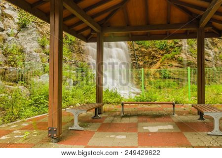 Beautiful Natural Waterfall Cascading Down Mountain Hillside Behind A Covered Wooden Gazebo.