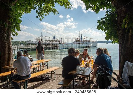 Hersching,germany-july 14,2018:people Sit In A Biergarten By The Shore Of Lake Ammersee As Paddle Bo