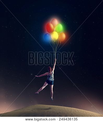 Young Girl Taking Off The Ground Holding Colorful Balloons.