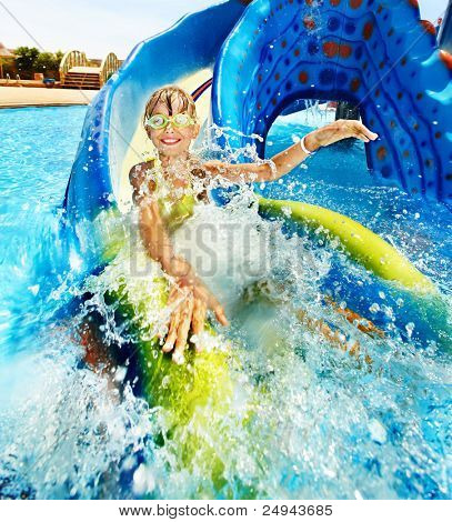 Child on water slide at aquapark. Summer holiday. poster