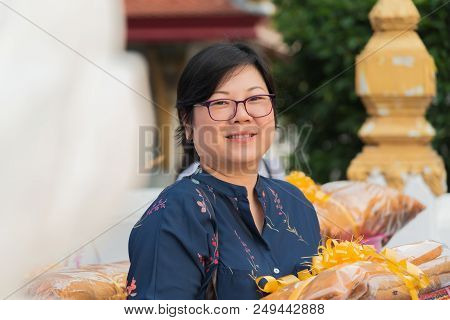 Asian woman 40s plump body hold the monk robe in parade for Thai monk ritual for change man to monk in ordination ceremony in buddhist in Thailand poster