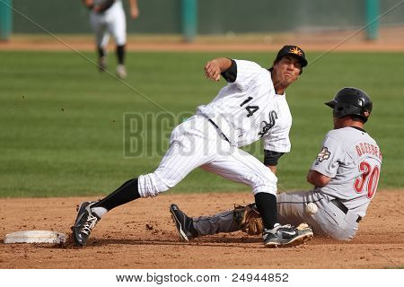 MESA, AZ - NOVEMBER 4: Salt River Rafters outfielder Jake Goebbert slides into Mesa Solar Sox infielder Tyler Saladino at Hohokam Park on November 4, 2011 in Mesa, AZ.