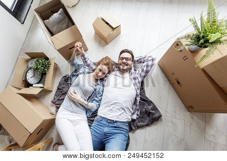 Couple Sitting On New Flat With Unpacked Boxes And Looking At Color Palette And Choosing In Which Co
