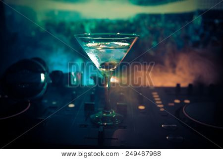 Glass With Martini With Olive Inside On Dj Controller In Night Club. Dj Console With Club Drink At M