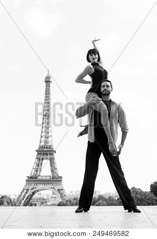 dance couple in front of eifel tower in paris, france. beatuiful ballroom dance couple in dance pose near eifel tower. romantic travel concept. sensual feeling and love poster