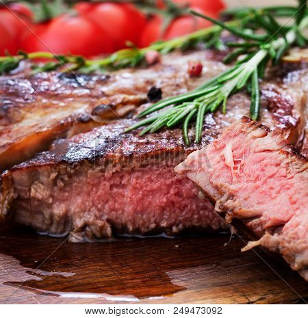 Sliced Beef Steak With Herbs And Tomatoes On Wooden Desk