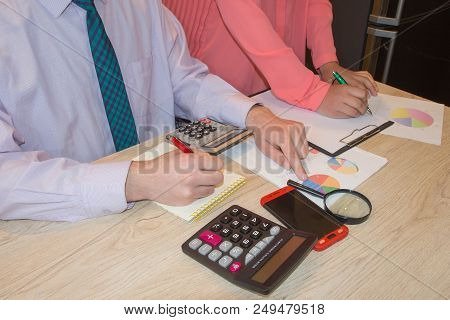 Businessmans Working On Office Desk With Calculator, A Computer, A Pen And Document. Business People