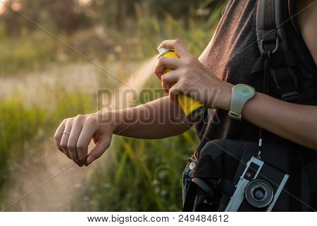 Woman Using Anti Mosquito Spray Outdoors At Hiking Trip. Close-up Of Young Female Backpacker Tourist