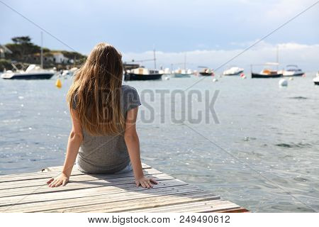 Back View Portrait Of A Woman Alone Contemplating The Sea On Summer