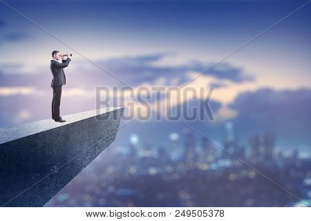 Business Vision Concept With Businessman On Concrete Cliff Above Blured City Holding And Looking Tro